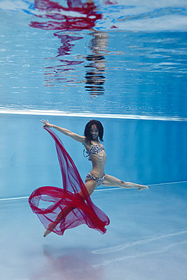 Woman diving with red cloth - p1310m1168569 by Uwe Ditz