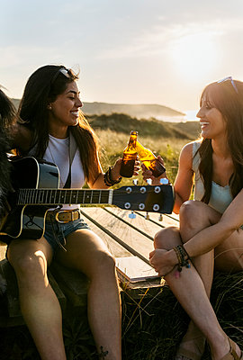 Two happy women with guitar clinking beer bottles on boardwalk in dunes - p300m2114748 by Marco Govel