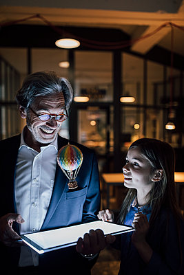 Happy senior buisinessman and girl with hot-air balloon and shining tablet in office - p300m2154891 by Gustafsson