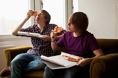 Two boys eating delivery pizza  - p30118953f by Andreas Stamm