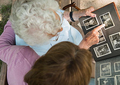 Senior woman sitting on park bench with granddaughter, looking at old photograph album - p429m942742f by Uwe Umstaetter