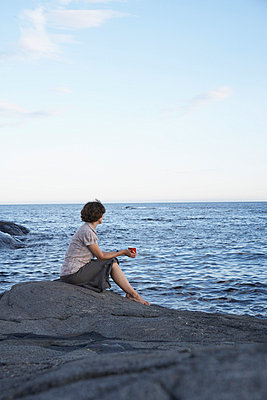 Woman sitting on a rock drinking coffee - p4641265 by Elektrons 08