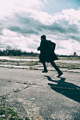 Silhouetted male figure running  - p794m1476580 by Mohamad Itani