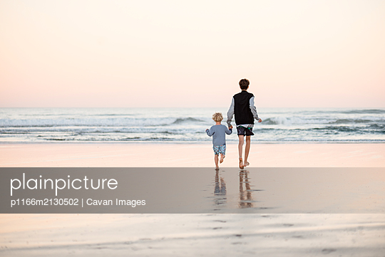 Toddler boy holding teenage brother's hand at beach - p1166m2130502 by Cavan Images