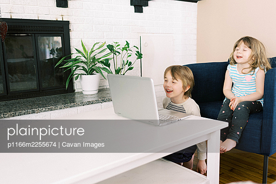 Two small children at laptop in living room during video call online - p1166m2255674 by Cavan Images