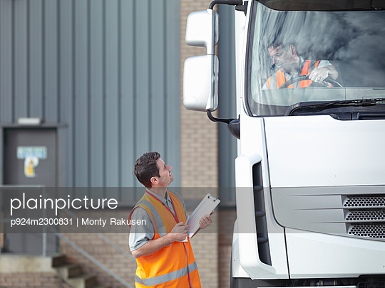 UK, Truck driver talking to driving instructor - p924m2300831 by Monty Rakusen