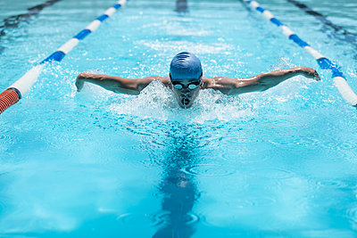 Young Caucasian male swimmer swimming butterfly stroke in swimming pool - p1315m2091026 by Wavebreak