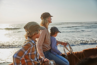 Chile, Vina del Mar, mother with two sons riding horses on the beach - p300m2070645 by Stefan Schütz