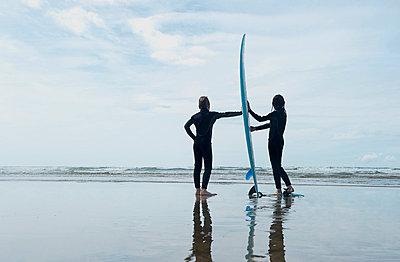 Children holding surf board on beach - p42911841f by Adie Bush