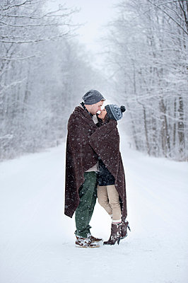 Romantic young couple kissing in snowy forest, Ontario, Canada - p429m2050896 by Sara Monika