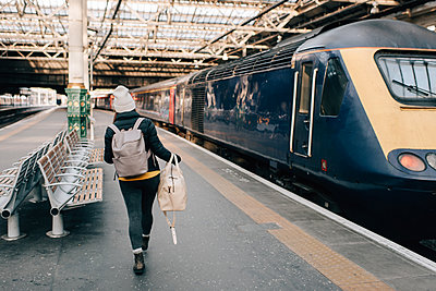 Woman walking to train at platform, Edinburgh, Scotland - p429m2098556 by Sara Monika