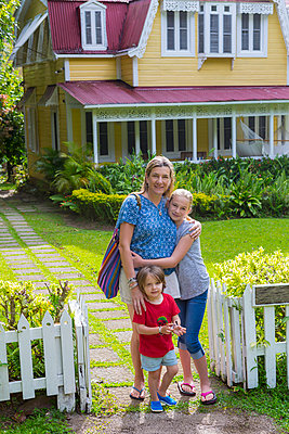 Caucasian mother with son and daughter in front view house - p555m1490993 by Marc Romanelli