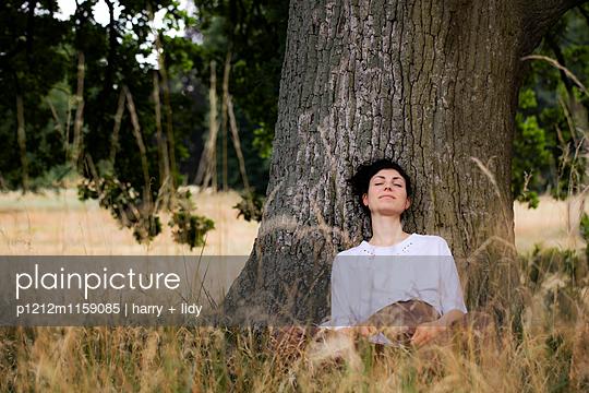 Junge Frau sitzt unter einem Baum - schläft - p1212m1159085 von harry + lidy
