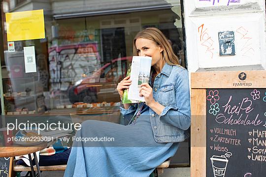 Frau sitzt im Strassencafe - p1678m2293091 von vey Fotoproduction