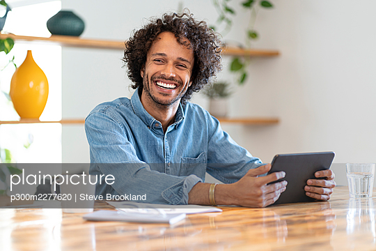 Cheerful businessman looking away while holding digital tablet on table at home - p300m2277620 by Steve Brookland