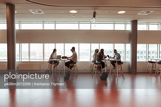 Full length of high school students studying at desks by window in cafeteria - p426m2072259 by Kentaroo Tryman