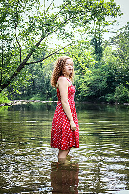Female teenager in red dress stands in creek - p1019m1462254 by Stephen Carroll