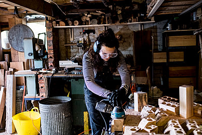 Woman with long brown hair wearing dungarees, safety glasses and ear protectors standing in wood workshop, using sander. - p1100m2164847 by Mint Images