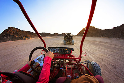 Cropped image of tourists riding beach buggies on dessert against clear sky - p1166m1037049f by Cavan Images
