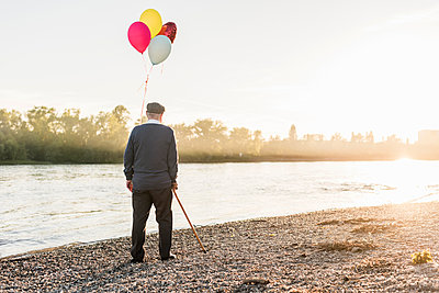 Back view of senior man with balloons standing at riverside in the evening - p300m1460704 by Uwe Umstätter