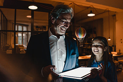 Happy senior buisinessman and girl with hot-air balloon and shining tablet in office - p300m2156096 by Gustafsson