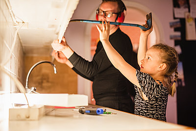 Father and daughter disassembling cupboards - p312m2139183 by Anna Johnsson