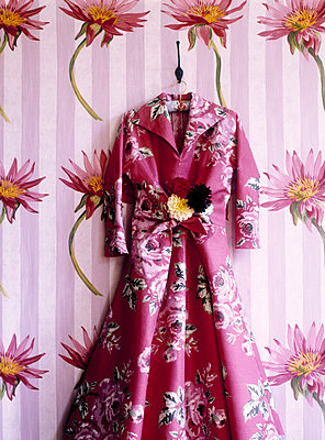 Pink vintage dress hangs against floral wallpaper - p349m2167670 by Polly Wreford