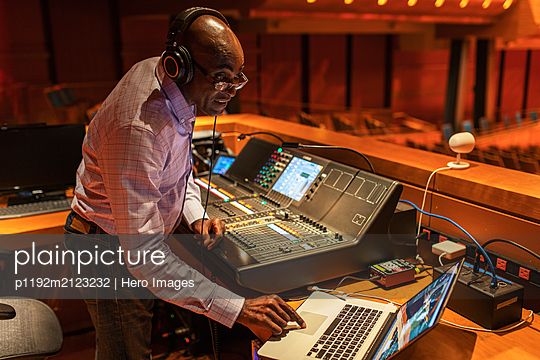 Male sound engineer using laptop at sound board in auditorium - p1192m2123232 by Hero Images