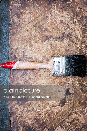 An old dirty paintbrush lying on a worn paper surface - p1302m2092523 by Richard Nixon