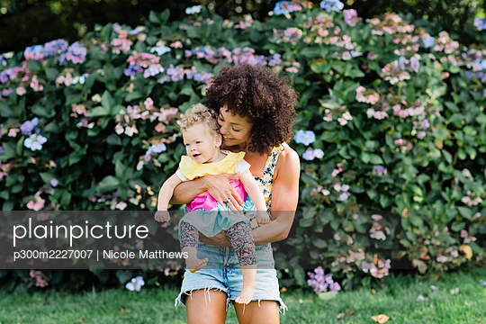 Mid adult woman carrying baby girl while standing against flowering plant at park - p300m2227007 by Nicole Matthews