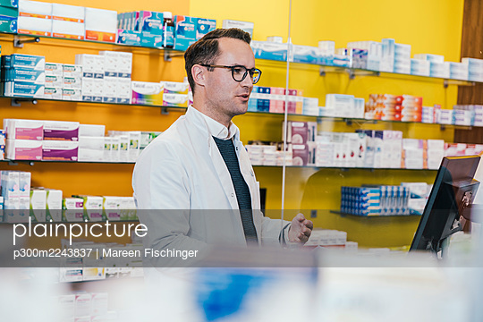 Pharmacist wearing lab coat while working in chemist shop - p300m2243837 by Mareen Fischinger