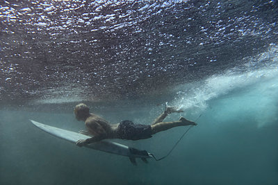 surfer on surfboard, underwater shot - p1166m2157297 by Cavan Images