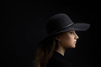 Profile of sad young woman wearing black hat against black background - p300m1568355 von Philipp Dimitri