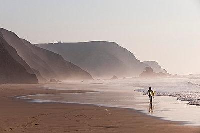 Portugal, Surfer walking on beach - p300m982009f by Michael Reusse