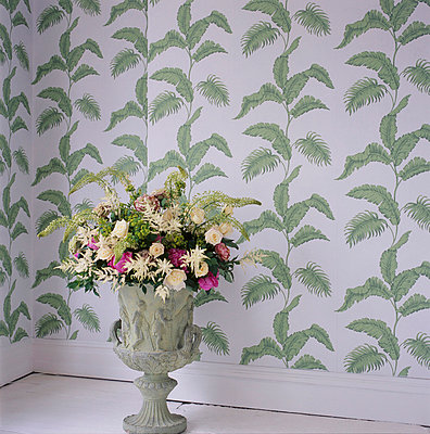 Green patterned wallpaper and a stone urn with flower display - p349m695189 by Emma Lee