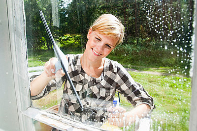 Girl washing window outside - p4265600f by Tuomas Marttila