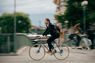 Full length of confident businessman cycling on bridge - p426m2145610 by Maskot