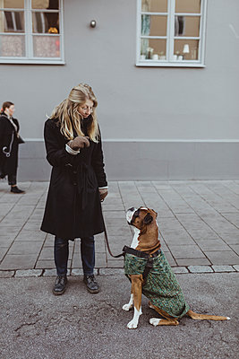 Full length of young woman standing with boxer dog against building in city - p426m2194779 by Maskot