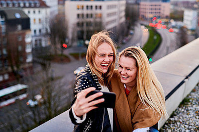 Two girlfriends take selfies on a rooftop - p890m2231026 by Mielek