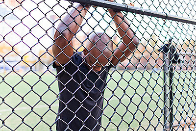 Man behind a chain link fence - p924m711079f by Steve Prezant