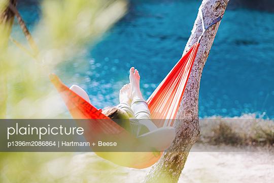 Frau liegt entspannt in Hängematte am Meer - p1396m2086864 von Hartmann + Beese