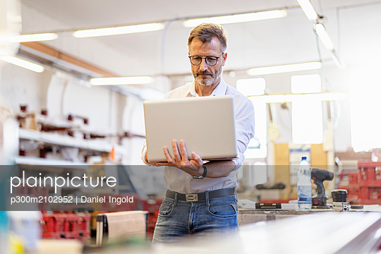 Businessman using laptop in factory - p300m2102952 by Daniel Ingold