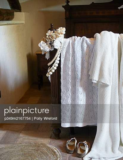 White lace and floral accessories and necklaces on vintage bed in Sicilian home - p349m2167754 by Polly Wreford