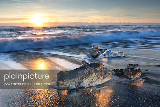 Pieces of glacier ice washed up on black volcanic sand beach at sunrise, near Jokulsarlon Glacial Lagoon, South Iceland, Polar Regions - p871m1506629 by Lee Frost