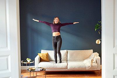 Young woman dancing on sofa - p1124m1589221 by Willing-Holtz