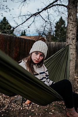 Teen girl sitting on hammock in backyard - p1166m2201314 by Cavan Images