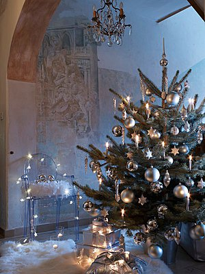 Decorated Christmas tree with lit candles in front of cherubs arranged on modern, transparent plastic chair - p1183m997815 by Manduzio, Matteo