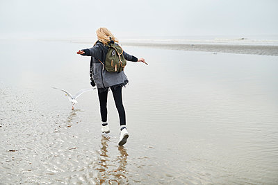 Netherlands, back view of young woman with backpack walking behind a seagull on the beach - p300m1586951 by Markus Mielek