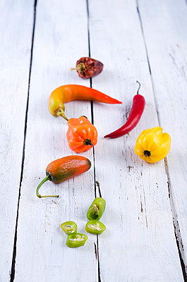 Colored chilis on wooden table - p300m838614f by Doris.H