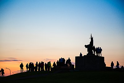 Silhouette of crowd of people around monument at sunset, Reykjavik, Iceland - p429m1135598 by Tim E White